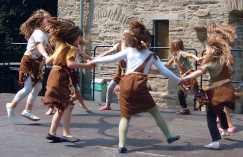 Tanzende Kinder in Steinzeit-Verkleidung